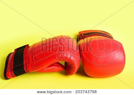 Pair Of Red Boxing Gloves For Wrestling Isolated On Yellow