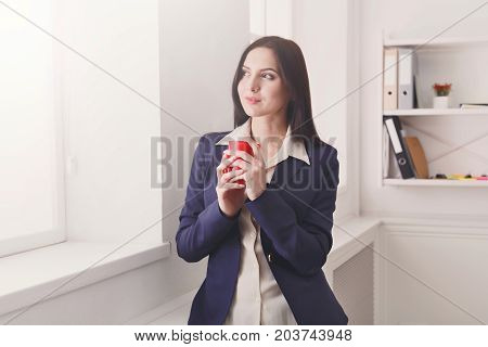 Coffee break. Pensive elegant business woman in formal wear standing at workplace and looking through window with cup