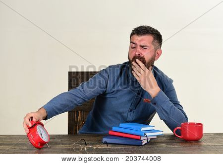 Man With Tired And Sleepy Face Sits At Wooden Table