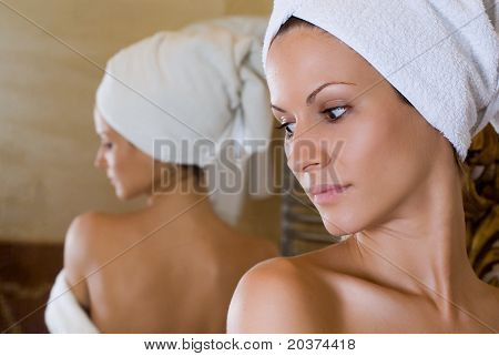 girl looking at the mirror over the sholder, spa and wellness concept