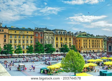 Krakow/Poland- August 15, 2017: view of main Market Square with walking tourists, souvenirs and flowers sellers, horse carriages  and colorful old houses on background, sunny summer day, blue sky