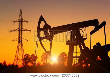 Industrial landscape. Oil Field. Oil pump against background of dawn and high-voltage pylon