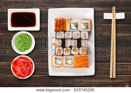 Japanese food restaurant delivery - sushi maki, unagi and roll platter set isolated on brown wood background, above view
