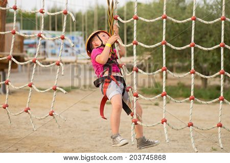Cute boy enjoying a sunny day in a climbing adventure activity park. Boy at climbing activity in high wire forest park.