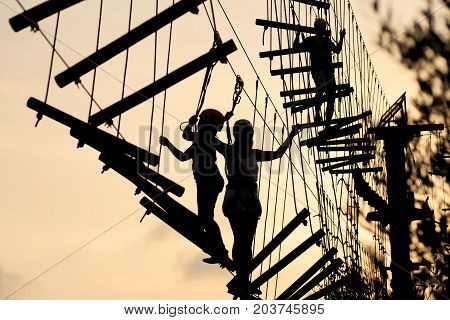 Silhouettes of people a walking on a rope ladder a rope park. Family hobby