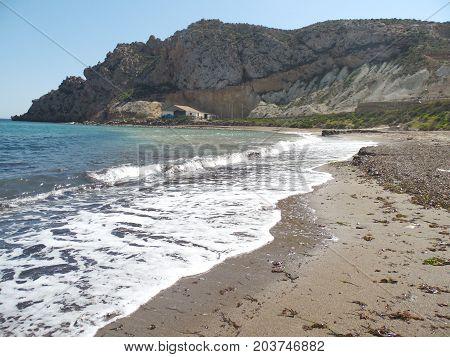 playa de arena blanca con montañas y olas