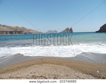 playa de arena blanca con olas e isla