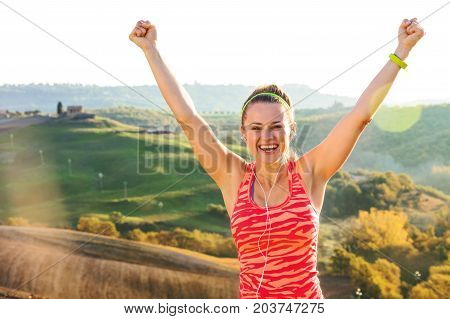 Smiling Active Woman Against Scenery Of Tuscany Rejoicing