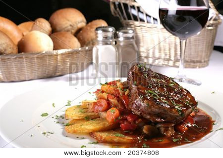 nice, juicy steak well done, served with vegetables and red wine, focus on parsley on the top