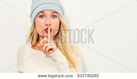 Happy young woman making a quiet gesture on a white background