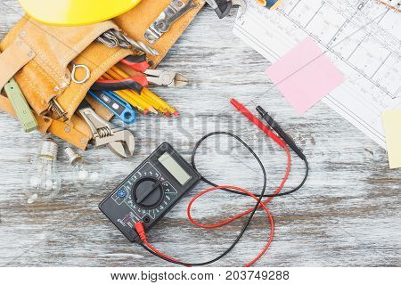 Set of construction tools drawings and multimeter on the wooden background