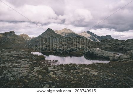 High Altitude Rocky Landscape And Little Lake. Majestic Alpine Landscape With Dramatic Stormy Sky. W