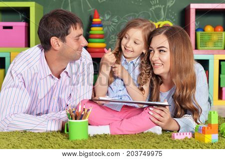 Little girl with plaits sitting on floor and drawing while her parents lying nearby