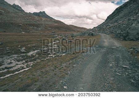Dirt Mountain Road Crossing Alpine Slopes And Meadows With Dramatic Stormy Sky And Panoramic View. P