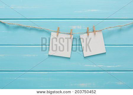 White blank cards on rope, blue wooden background. Creative reminder, small sheets of paper on old clothespin, bright memo backdrop