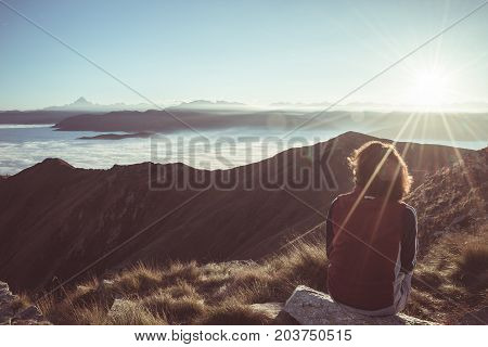 Female hiker reaching her goal at the mountain top and looking at majestic panoramic view of the Alps with mountain peak in the background. Wide angle view at sunset in backlight toned image vintage filter split toning.