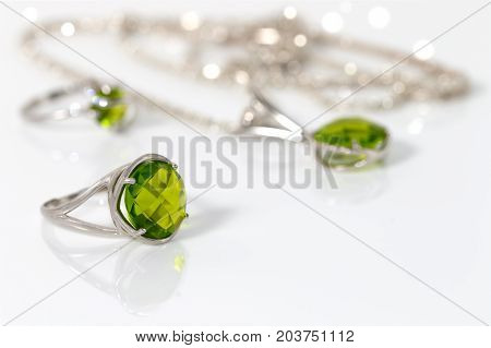 Beauty silver ring with chrysolites on background pendant and ring on white acrylic desk.