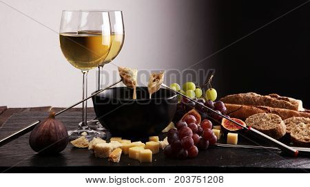 Gourmet Swiss Fondue Dinner On A Winter Evening With Assorted Cheeses On A Board Alongside A Heated