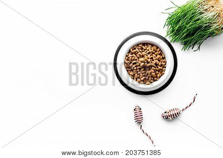 large plastic bowl of pet - cat food with toys on white table background top view mockup