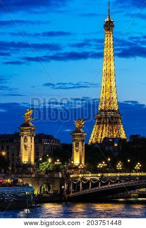 Paris France - July 01 2017: Beautiful night illumination of Eiffel Tower and Pont Alexandre III Bridge over river Seine decorated with ornate art nouveau lamps and sculptures.