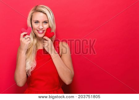 Happy young woman holding heart cushions on a red background