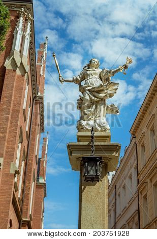Krakow/Poland- August 15, 2017: symbol of justice stone statue - woman figure, holding golden arrows and scepter - near Faculty of law building, part of Jagiellonian University