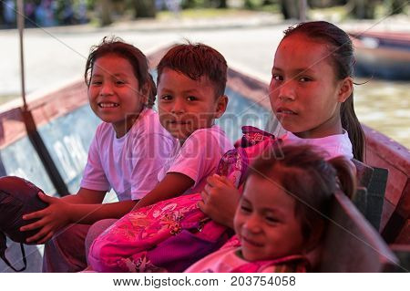 June 6 2017 Misahualli Ecuador: huaorani children lit by the light filtered by the colored tarp of the small boat on their way home from school