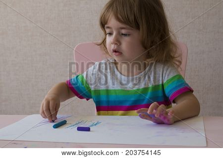 children cute or kid girl learning for coloring or hand drawing paint on white paper and colorful table with chair at nursery or pre school.