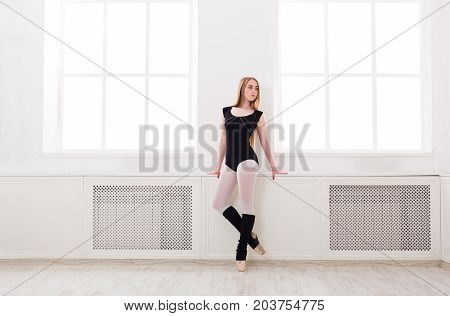 Young graceful ballerina in black at ballet class stands. Classical dancer in white hall, copy space