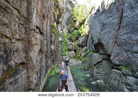 SZCZELINIEC POLAND - JULY 29 2017: Tourists hike the mountains along the trial between the rocks in Table Mountains National Park