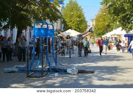 A man in the square does gymnastic exercises on uneven bars and a crossbar. Day of the city. Zhitomir of the year 1133. September 2017 Ukraine.