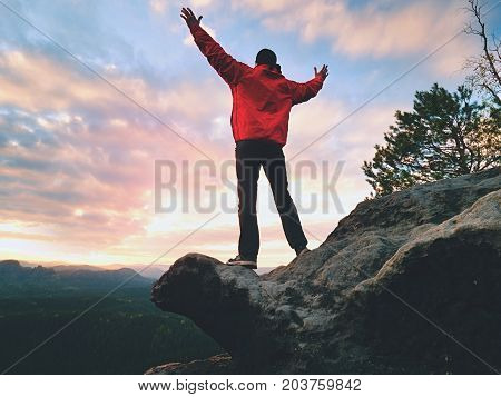 Happy Man Gesture Of Triumph With Rams In  Air. Funny Hiker On Peak Of Rock