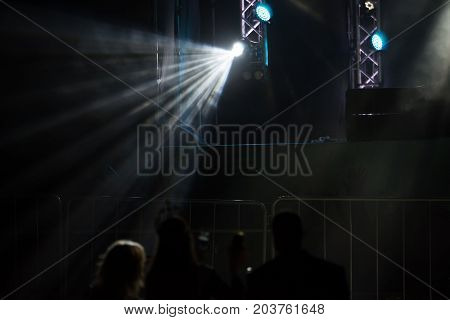 The girl with the crown under the fire of searchlights during a beauty contest