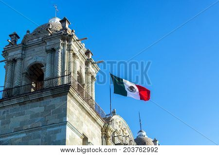 Mexican flag flying over Our Lady of the Assumption church in Oaxaca Mexico on March 4 2017