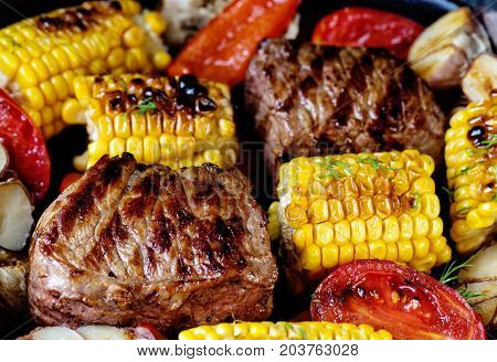 Food background of baked meat and corn. The concept of healthy natural food. Traditional cuisine.