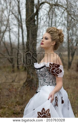 Beautiful young lady in gorgeous vintage white dress in the forest in the fog. Late autumn cold. Melancholy