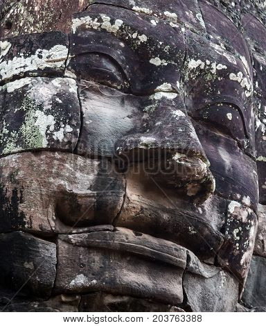 Ancient stone faces of king Bayon Temple Angkor Thom Cambodia. monument Khmer architecture Kampuchea.