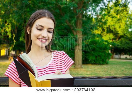 Young smiling woman sitting with diary making some notes in beautiful city park