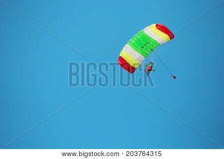 Two people on a multi-colored parachute in the sky. The concept of movement and freedom.