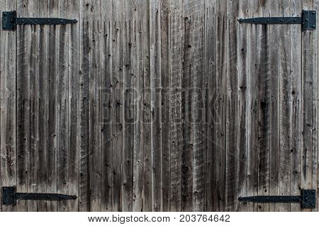 Weathered wood gate with black hasp hinges
