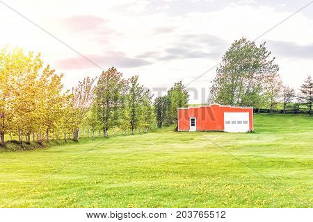 Landscape View Of Farm In Ile D'orleans, Quebec, Canada With Red Painted Vintage Shed, Field, Dandel