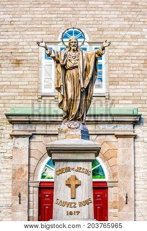 Ile D'Orleans Canada - June 1 2017: Saint-Jean red painted church with stone architecture and Jesus Christ statue with outstretched open welcome arms cross and sign