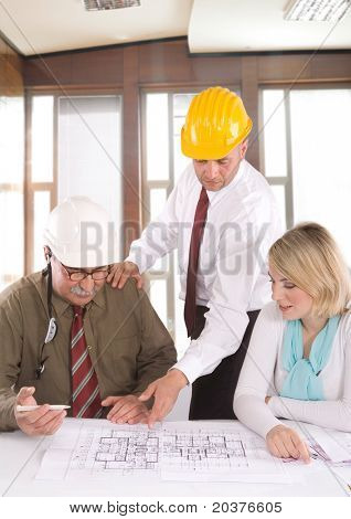 team of architects at the meeting looking at blueprints