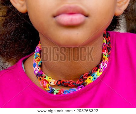 little girl with necklace made with colored rubber loom bands