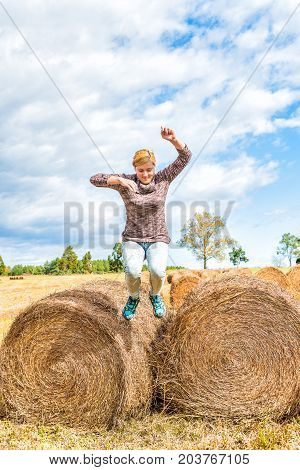 Young woman in air jumping off hay roll bales in countryside field farm