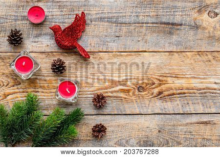 bird toys and candles to decorate christmas tree for new year celebration with fur tree branches on wooden table background top veiw mockup