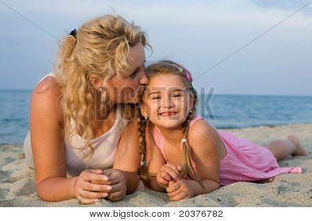 mother kissing her little daughter at the beach while having summer holiday