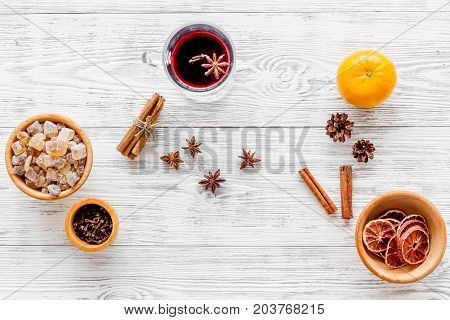 Hot mulled wine or grog cooking for new year celebration with oranges and spices ingredients on light table background flat lay mockup