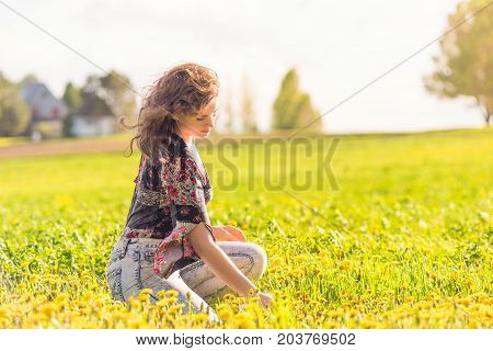 Young Happy Woman Sitting In Yellow Dandelion Farm Field During Sunset By House In Ile D'orleans, Qu