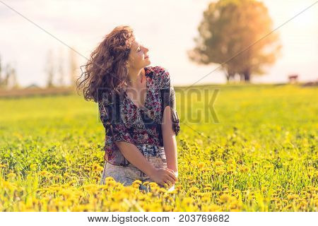 Profile Portrait Of Young Smiling Woman Sitting In Yellow Dandelion Farm Field During Sunset By Hous